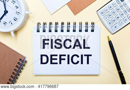 On A Light Background, A White Alarm Clock, A Calculator, A Pen And A Notebook With The Text Fiscal