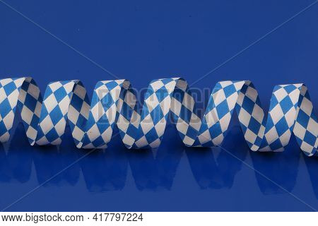 Blue And White Bavarian Paper Streamer Are Lying On A Blue Ground