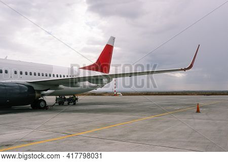 Unloading Baggage From The Plane At The Airport. Transportation Of Cargo And Passengers By Plane. Pa