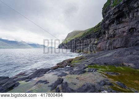 Rocky Faroese Shore On A Cloudy Day. Cliffs Of Kalsoy Island. Late Cloudy Morning In The Wild Fjords