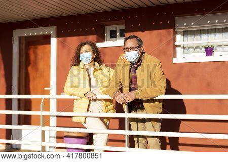 Senior Couple With Medical Mask Observing The Street From The Porch Of Their Home. Concept Of Uncert