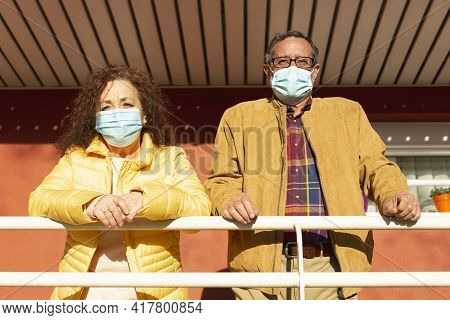 Portrait Of Two Senior Citizens Observing The Outside From The Porch Of Their Home. They Are Wearing
