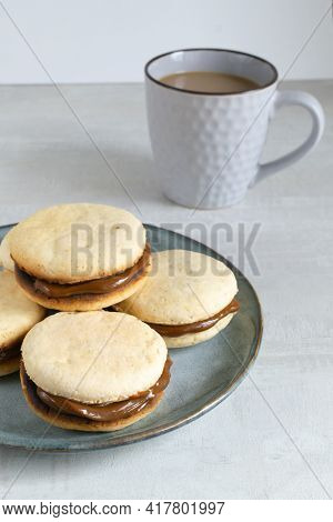 Alfahores Cookies With Condensed Milk On A Gray Plate With A Cup Of Coffee. Traditional Homemade Bis