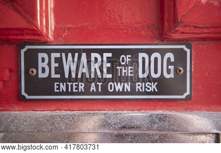 Beware Of The Dog Sign On A Red Door