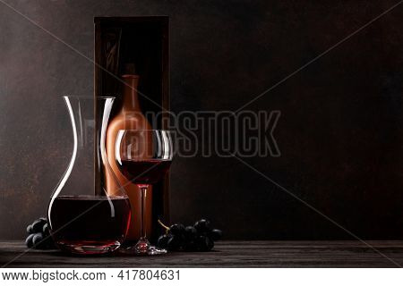 Decanter with red wine, wine bottle in box, grapes and wineglass with copy space