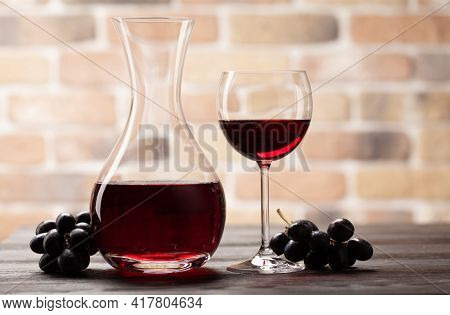 Wine decanter, glass of red wine and grapes. With copy space