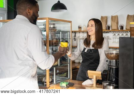 Friendly And Helpful Waitress Is Serving An African-american Male Customer, Preparing And Giving Pap