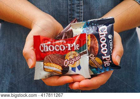 Tambov, Russian Federation - October 30, 2020 Different Tastes Choco-pie Snack Cakes In Woman Hands.
