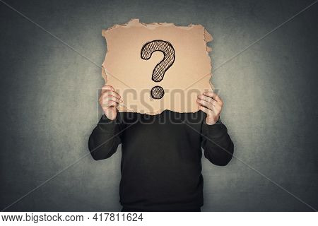 Anonymous Man Covers His Head Using A Torn Cardboard Sheet, Like A Mask, With Drawn Question Mark. I