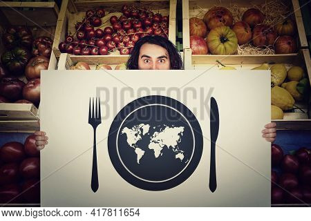 Global Hunger, Food Supply Issue. Shocked Man Holding A Warning Message Banner In Front Of A Grocery