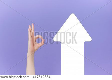 Unrecognizable Young Male Makes Thumb Up Gesture Near White Paper Arrow, Demonstrates Approval Or Ag