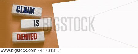 Claim Is Denied On Wooden Blocks On Brown Background With Copyspace. Business Financing Sponsorship