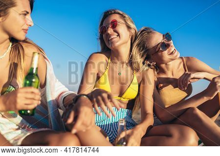 Happy Young Women Sitting On The Beach. Group Of Friends Enjoying On Beach Holiday.