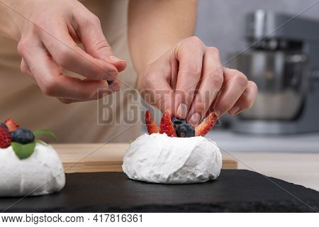 Hands Of Pastry Chef Decorates Cake With Fresh Strawberries And Blueberries. Cake Anna Pavlova.