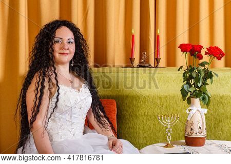 A Jewish Bride In A White Wedding Dress Without A Veil Sits At A Table With Flowers Before The Chupp