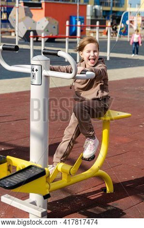 Adorable Little Kid Girl Making Exercises On Sports Training Apparatus At The Gym