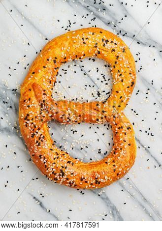 Freshly Baked Homemade Pretzel With Black And White Sesame Seeds On A Marble Background. Traditional