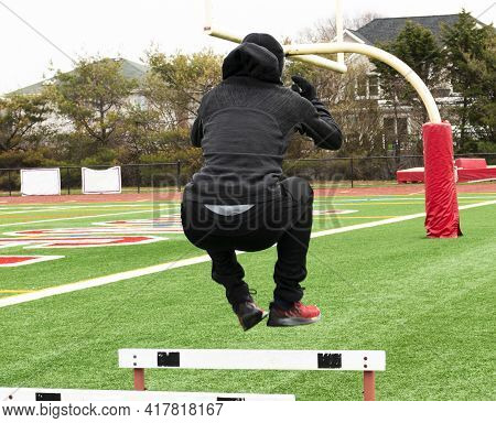 Rear View Of A Track And Field Athlete Jumping Over Hurdles On A Green Turf Field Wearing All Black.