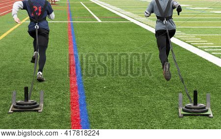 Rear View Of Two High School Male Track Runners Pulling Sleds With Weights On A Green Turf Field Dur