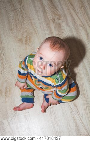 Eight Month Old Baby Boy Sitting On The Floor, Top View