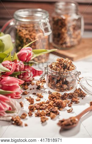 Mason Jar With Granola Breakfast Cereal With Nuts. Wooden Spoon With Scattered Granola And A Bouquet
