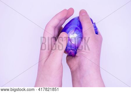 Close Up Of Game With Two-color Blue And Pink Slime In Someone's Hands On A White Background. The Mu