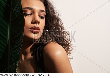 Portrait Of Brunette Woman With Modern Make Up And With Long Curly Hair Near Accessories Green Leaf.