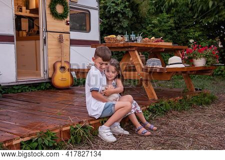 Boy And Girl Are Sitting At Trailer Truck Home On Wooden Floor, Holding Fluffy Rabbit Bunny In Their