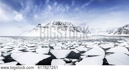 Panorama of the pristine mountains and floating pack ice, in the Fjords of Svalbard, a Norwegian archipelago between mainland Norway and the North Pole