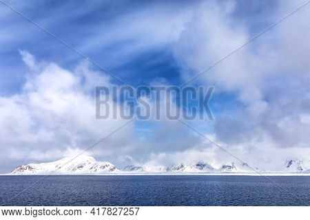 Pristine snow covered mountains and blue summer sky. Svalbard, a Norwegian archipelago between mainland Norway and the North Pole