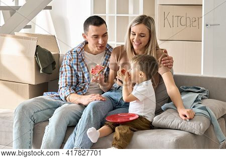 Happy Young Family Sitting On Sofa With Kid Feeding With Bread And Jam. Joyful Family In Living Room