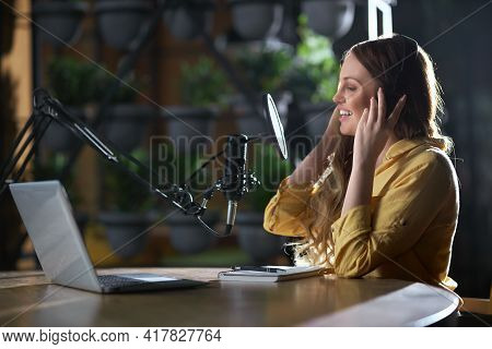 Side View Of Cute Young Attractive Woman Smiling And Recording Songs Or Interesting Information For