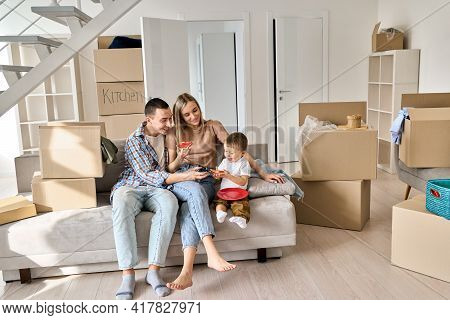 Happy Young Parents Sitting On Sofa With Kid Relaxing In New Home In Relocation. Joyful Family In Li