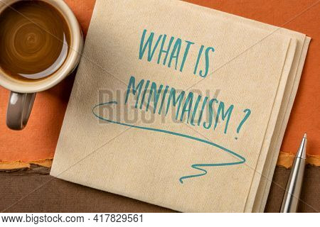 What is minimalism? Handwriting on a napkin with a cup of coffee. Simplicity and lifestyle concept.