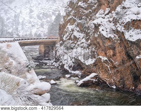 highway bridge over the Poudre River at Big Narrows, early spring scenery with a heavy snowstorm