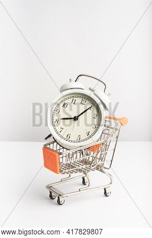 A Supermarket Cart With Old Vintage Alarm Clock On White Background. Shopping, Purchases, Supermarke