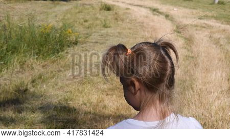 Toddler Girl Turns Her Head Standing At Dirt Road In Countryside. Kid Hair Tied With Colorful Rubber