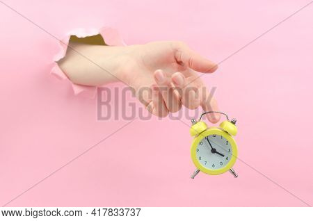 A Female Hand Through The Background Holds A Yellow Retro Alarm Clock. At 15.55 Hours, The Concept O