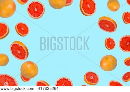 Creative Idea With Fresh Grapefruit Sliced On Pastel Blue Background, Fruits Frame With Space For Te