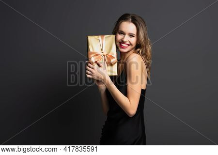 Happy Young Woman In Black Slip Dress Holding Wrapped Gift Box On Grey.