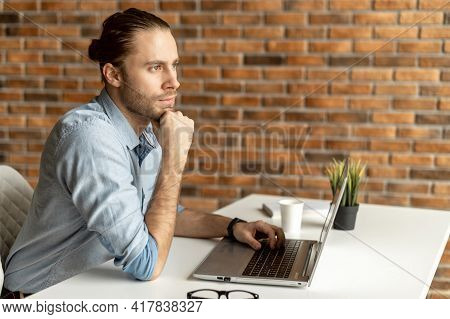 Handsome Male Businessman Looking For Solving Business Tasks, A Hipster With Laptop Sitting At The D