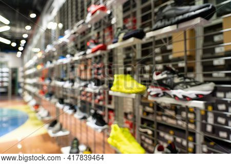 Abstract Blur Sport Shoes On Shelves In Sneakers Shop Background.