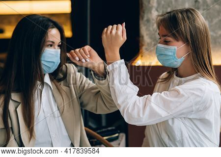 Co-workers In Protective Masks Giving High Five With Elbows.