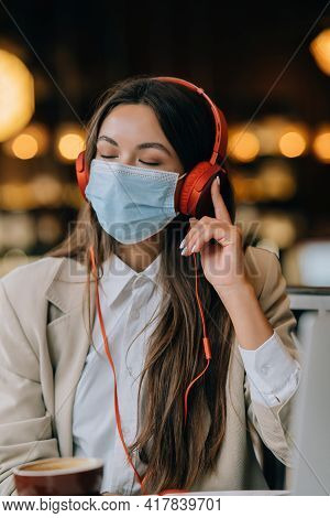A Girl Sitting In A Coffee Shop With Headphones. Coronavirus Outbreak.