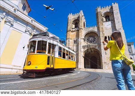 Young Woman Tourist Photographing With Phone Famous Retro Yellow Tram 28 On The Street In Lisbon Cit