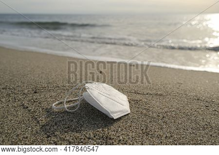 Discarded Disposable Face Mask Floating On Dirty Sea Shore, Covid19 Pandemic Pollution