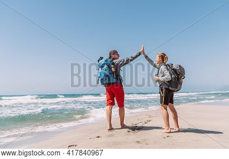 Father And Teenager Son With Backpacks Making High Five On Sandy Seaside Beach During Lycian Way Tre