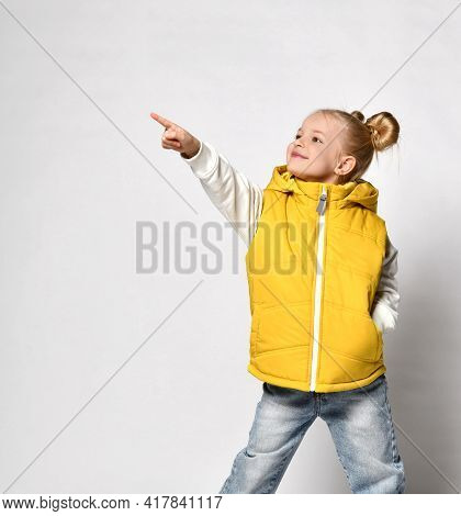 Pretty Smiling Blonde Girl In A Yellow Puffy Vest Is Standing With Her Hand In Her Pocket And Pointi