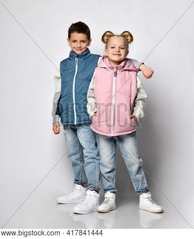 Studio Shot Of Little Brother With Sister In Warm Outerwear Blue And Pink Vests, Jeans, Sneakers And