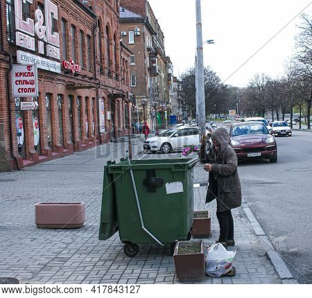 Dnepropetrovsk, Ukraine - 04.21.2021: Poor Hungry Woman Looking For Food In A Trash Can On The Stree